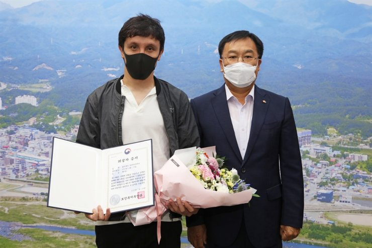 Yuldashev Aliakbar from Kazakhstan, left, poses with Yangyang County head Kim Jin-ha at his office in Yangyang, Gangwon Province, Tuesday. Courtesy of Yangyang County Office