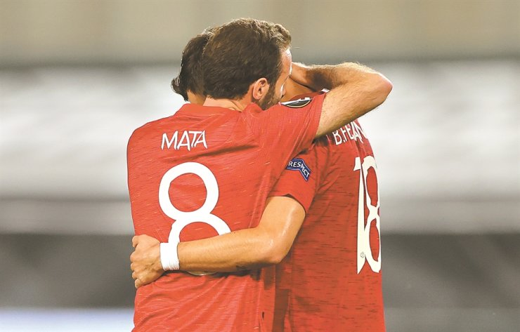 Manchester United's Bruno Fernandes, right, celebrates with team mate Juan Mata after scoring the 1-0 penalty goal during the UEFA Europa League quarter final football match between Manchester United and FC Copenhagen in Cologne, Germany, Monday. / EPA-Yonhap