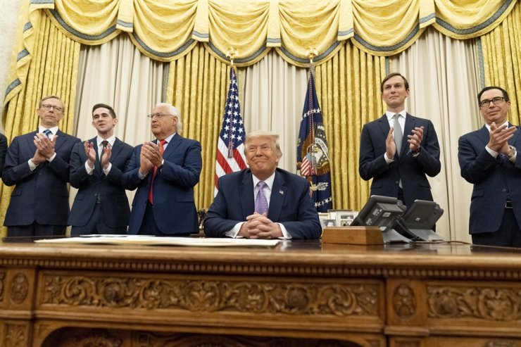 President Donald Trump, accompanied by from left, U.S. special envoy for Iran Brian Hook, Avraham Berkowitz, Assistant to the President and Special Representative for International Negotiations, U.S. Ambassador to Israel David Friedman, Trump's White House senior adviser Jared Kushner, and Treasury Secretary Steven Mnuchin, applaud in the Oval Office at the White House, Wednesday, Aug. 12, 2020, in Washington. AP