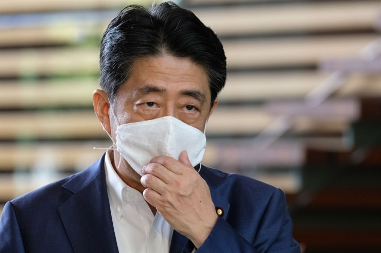 Japan's Prime Minister Shinzo Abe wearing a face mask arrives at the Prime Minister's office in Tokyo on August 24, 2020. Abe earlier in the day returned to hospital on August 24 for more medical checks, a government spokesman said, a week after a first visit that fuelled growing speculation about his health. (Photo by Kazuhiro NOGI / AFP)