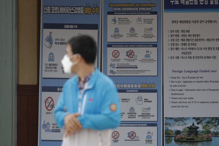 A man wearing a face mask walks near banners showing precautions against the new coronavirus at the Gyeongbok Palace in Seoul, Friday, July 31, 2020. AP