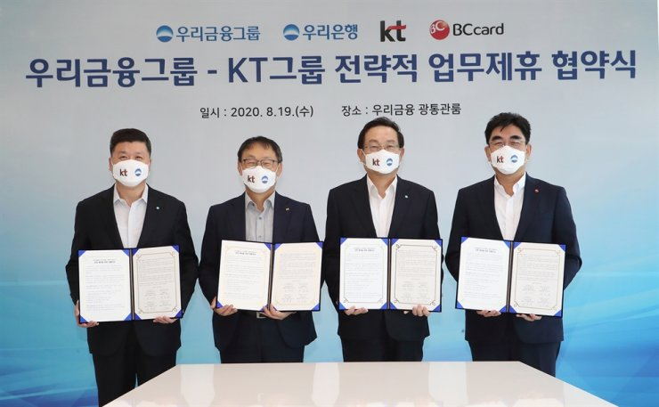 KT CEO Koo Hyun-mo, second from left, and Woori Financial Group Chairman Sohn Tae-seung, third from left, hold copies of an agreement after the two companies signed a non-binding memorandum of understanding (MoU) to jointly promote digital finance-centric business at Woori Bank's headquarters in downtown Seoul, Wednesday. Courtesy of KT