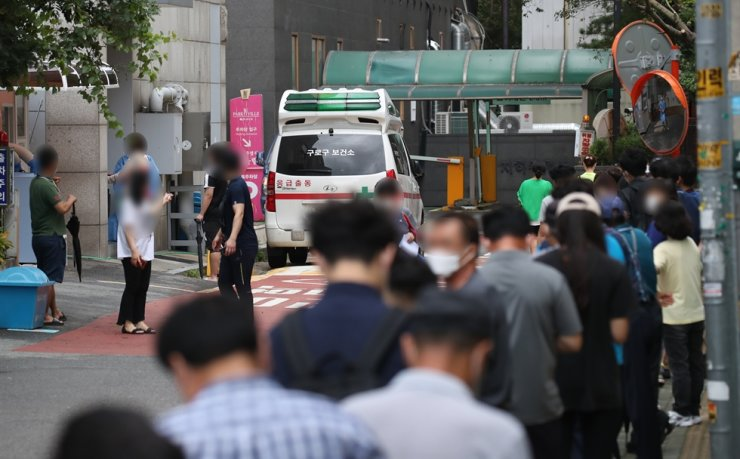 Residents of Guro-gu in southwestern Seoul wait to be tested for COVID-19 outside the district health center, Thursday. /Yonhap