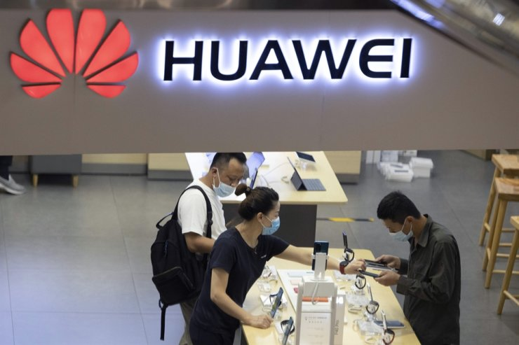 In this Wednesday, July 15, 2020 file photo, visitors wearing masks to curb the spread of the coronavirus look at the latest products at a Huawei store in Beijing. AP-Yonhap