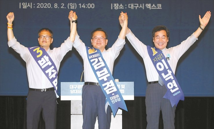 From right, Reps. Lee Nak-yon, Kim Boo-kyum and Park Ju-min, all candidates for the ruling Democratic Party of Korea's leadership race, hold hands before delivering speeches to party members at EXCO in Daegu, Sunday. The party will elect its new chairperson during its convention on Aug. 29. Yonhap