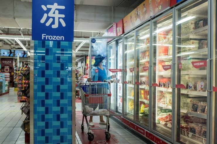A woman looks at frozen food products in a supermarket following an outbreak of the coronavirus disease (COVID-19) in Beijing, China, August 13, 2020. Reuters-Yonhap