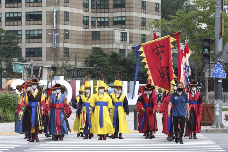Korean Imperial guards wearing face masks to help protect against the spread of the coronavirus cross a road in Seoul, Wednesday, Aug. 5, 2020. AP