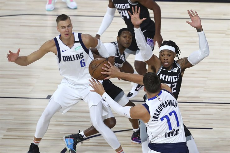 [PAP20200805054501055]Dallas Mavericks guard Luka Doncic, front, passes the ball to forward Kristaps Porzingis, left, as Sacramento Kings center Richaun Holmes, right, defends during the first half of an NBA basketball game Tuesday in Lake Buena Vista, Fla. / AP-Yonhap