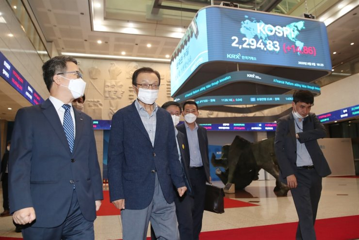 Ruling Democratic Party of Korea (DPK) leader Lee Hae-chan, second from left, walks with Korea Exchange CEO Jung Ji-won, first from left, at the nation's bourse operator Korea Exchange (KRX) located in Yeouido district in Seoul, Wednesday. A dozen of the ruling party lawmakers, finance ministry officials and key figures of the finance industry attended Wednesday's meeting about raising a 'K-New Deal' fund. / Yonhap