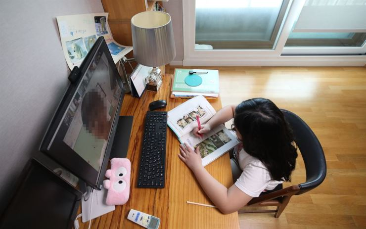 An elementary school student watches a lecture on a desktop computer at home in Songpa-gu, northeastern Seoul, Wednesday. Yonhap