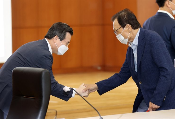 Ruling Democratic Party of Korea leader Lee Hae-chan, right, shakes hands with Vice Finance Minister Kim Yong-beom at the Korea Exchange's Seoul office on Yeouido, Wednesday, before announcing a plan to launch the K-New Deal fund. Yonhap