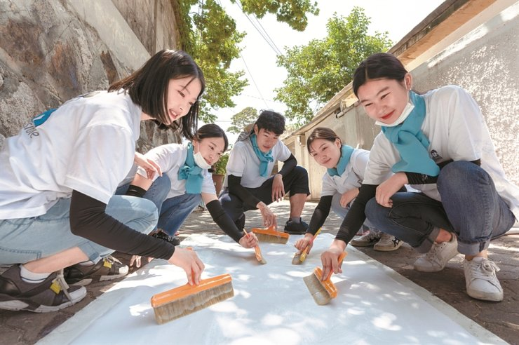 Daewoo E&C employees take part in the company's home repair activities for underprivileged households in this photo provided by the company, Sunday. / Courtesy of Daewoo E&C