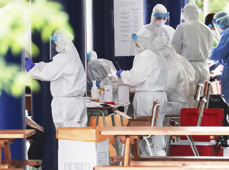 Medical inspectors examine students and faculty members of Jukjeon High School in Yongin, Gyeonggi Province, Thursday, to check their COVID-19 infection possibility. Yonhap