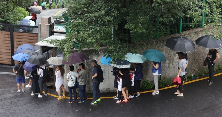 Visa applicants are lined up outside the Chinese Consulate in Seoul, Wednesday. Yonhap