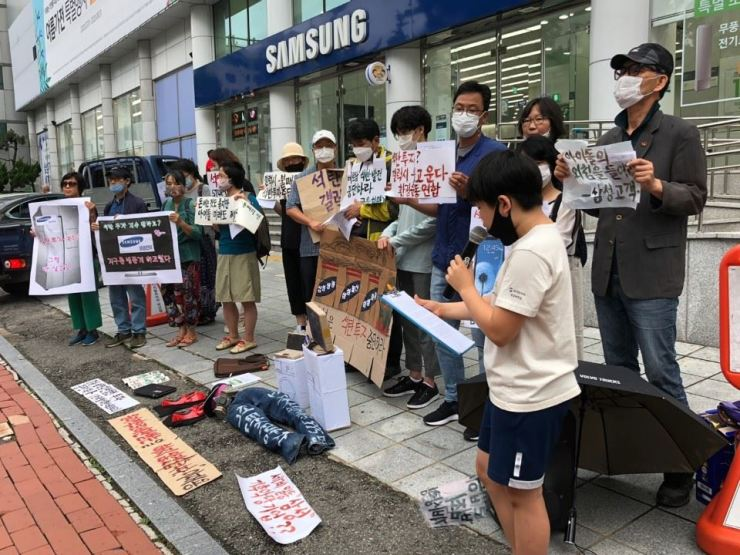A young student reads a letter to Samsung Electronics Vice Chairman Lee Jae-yong in a protest by a regional unit of the environmental group Climate Strike against Samsung affiliates' coal investments, held in front of a Samsung Electronics Service Center in Changwon, South Gyeongsang Province, Wednesday. / Courtesy of Climate Strike's South Gyeongsang Province chapter
