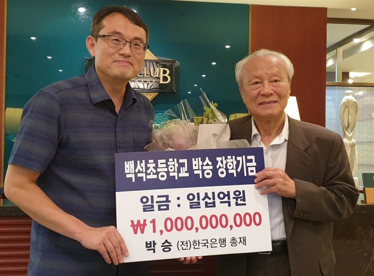 Former Bank of Korea Governor Park Seung, right, poses with Baeksuk Elementary School Principal Moon Hong-min at the school in Gimje, North Jeolla Province, Monday, after donating 1 billion won ($845,000) to the school. / Courtesy of Jeollabukdo Office of Education