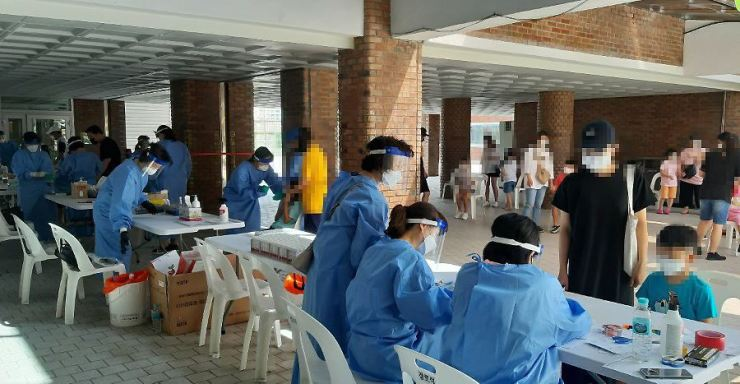 Health officials carry out COVID-19 testing at a makeshift testing facility in an elementary school in Chuncheon, Gangwon Province, Sunday, as at least two students there tested positive for the virus. / Yonhap