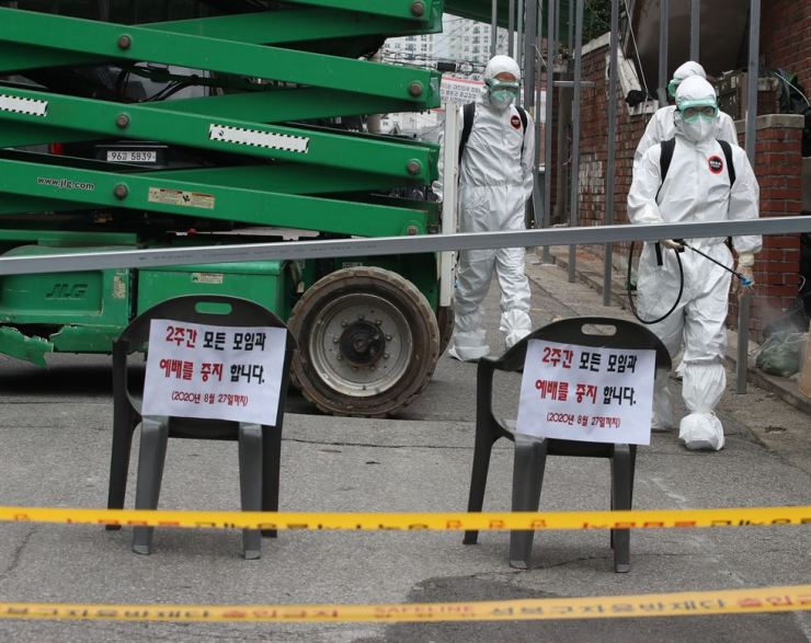 Health inspectors fumigate surroundings of Sarang Jeil Church in Seoul's Seongbuk-gu District, Friday, which the Seoul city government shut down after cluster infection of COVID-19 took place there. Yonhap