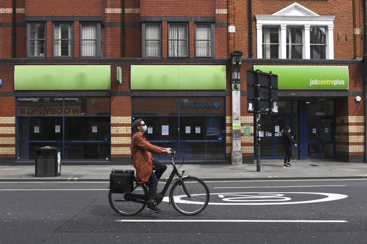 A woman wearing a face mask to protect against coronavirus, rides a bicycle past a job center in Shepherd's Bush, as the lockdown to curb the spread of coronavirus continues, in London in this April 30 file photo. / AP-Yonhap
