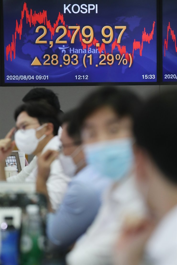 Dealers sit at their desks in a trading room at a branch of Hana Bank in Seoul, Aug. 4. Korea Times file
