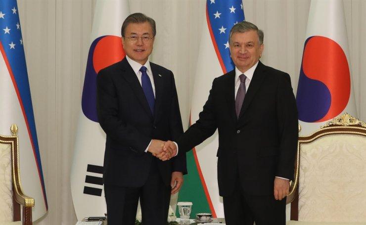 President Moon Jae-in and his Uzbek counterpart Shavkat Mirziyoyev, shake hands in Tashkent, in Uzbekistan, last year. Korea Times file