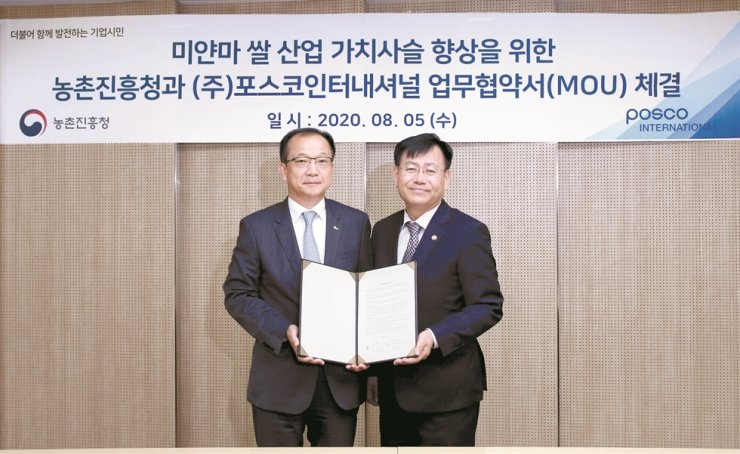 Posco International CEO Joo Si-bo, left, poses with Rural Development Administration Administrator Kim Kyeong-kyu during an MOU signing ceremony for support of Myanmar's farming market at POSCO Group's Seoul office, Wednesday. / Courtesy of POSCO International.
