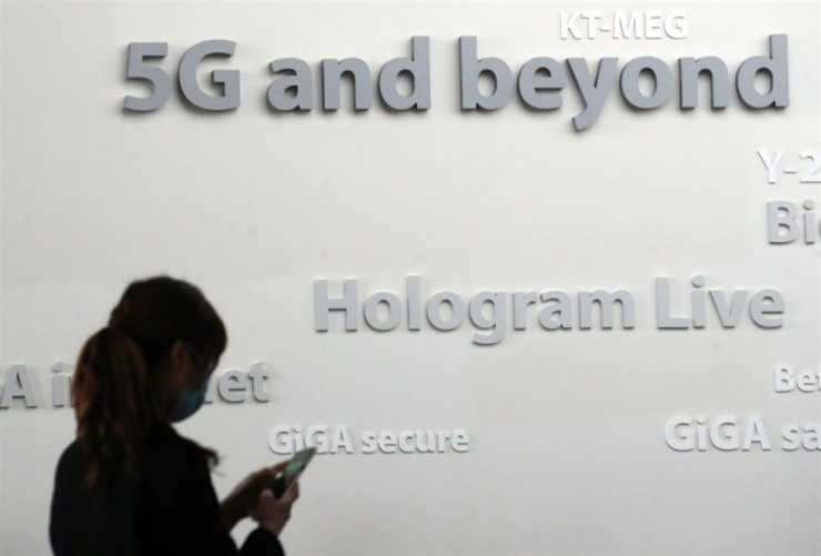 A woman using her smartphone passes by a 5G promotion sign set up in Gwanghwamun Square in Seoul. / Yonhap