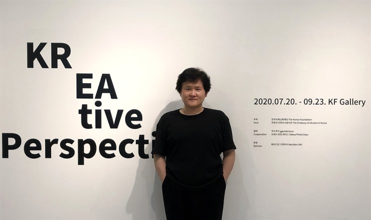 Photographer Jung Sung-tae poses at the entrance of an ongoing contemporary photo exhibition, titled 'KREAtive Perspectives,' jointly hosted by the Korea Foundation (KF) and the Embassy of Ukraine in Korea at the KF Gallery in Seoul. The exhibition runs through Sept. 23, featuring 160 works from 12 Ukrainian and Korean artists including Jung. / Courtesy of Jung Sung-tae