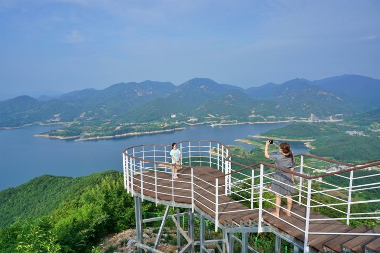 A woman takes a photo of her daughter at an observatory on Mount Bibong in Jecheon, North Chungcheong Province. / Courtesy of Korea Tourism Organization