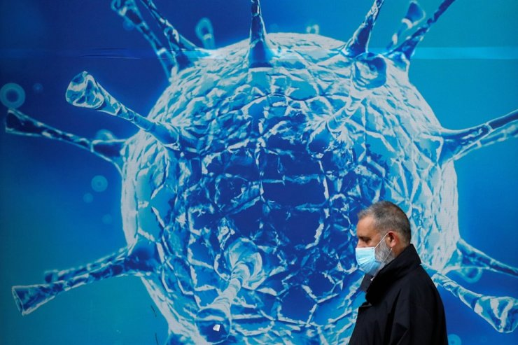 A man wearing a protective face mask walks past an illustration of a virus outside a regional science center in Oldham, Britain, Monday, as the city and surrounding areas face local restrictions in an effort to avoid a local lockdown being forced upon the region amid the COVID-19 outbreak. Reuters-Yonhap