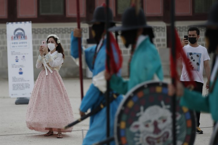 Visitors hold their smartphones while maintaining social distancing during a re-enactment ceremony of the changing of the Royal Guard at the Gyeongbok Palace in Seoul, Friday, July 31, 2020. AP