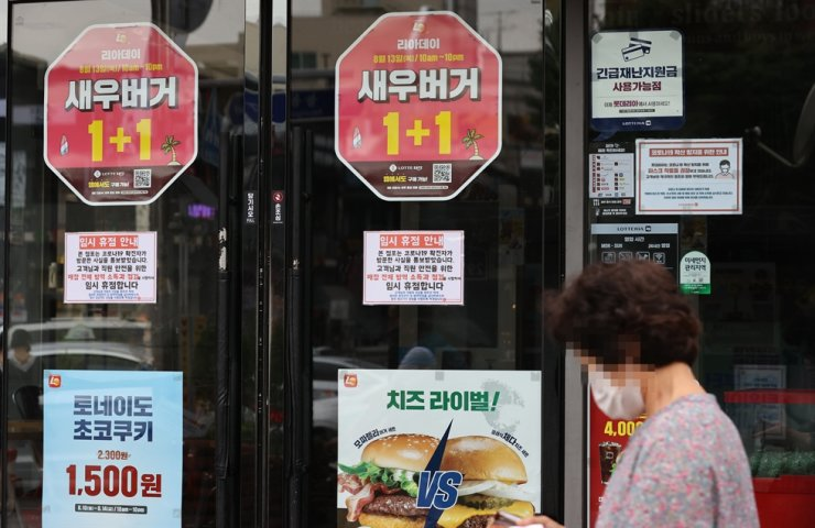 A woman passes by a notice of a temporary shutdown posted at the entrance of Lotteria's Gunja branch, Wednesday. At least 11 Lotteria employees have tested positive for COVID-19 since Tuesday. / Yonhap