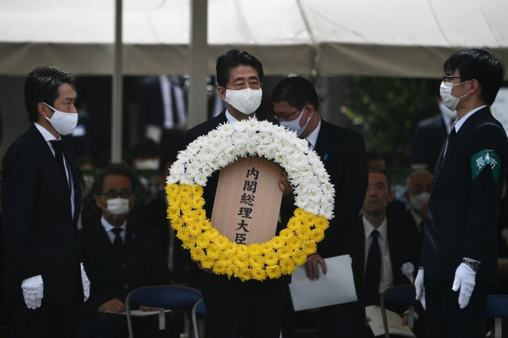 Japanese Prime Minister Shinzo Abe lays a wreath during a ceremony marking the 75th anniversary of the atomic bombing of Nagasaki, at the Nagasaki Peace Park on August 9, 2020. - Nagasaki was flattened in an atomic inferno three days after Hiroshima in 1945, twin nuclear attacks that rang in the nuclear age and gave Japan the bleak distinction of being the only country to be struck by atomic weapons. /AFP