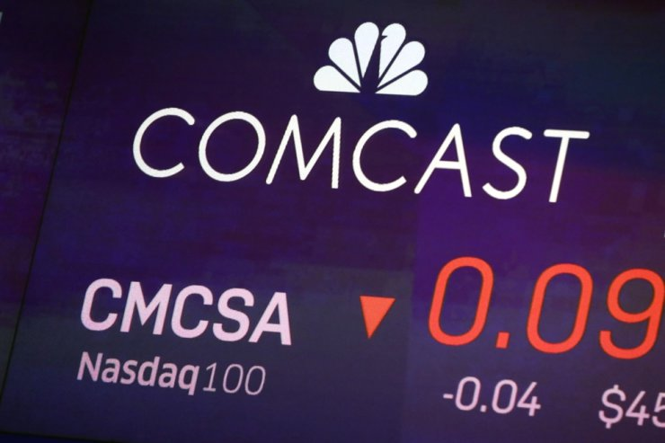 In this Oct. 1, 2019, file photo the symbol for Comcast appears on a screen at the Nasdaq MarketSite, in New York. The coronavirus pandemic took a toll on Comcast in the second quarter as movie theaters closed, theme parks shut down and advertisers cut back. AP-Yonhap