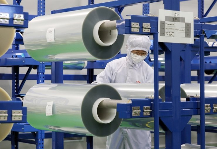 An employee at SKIET checks 'Flexible Cover Window' products, which the company recently started supplying to a global smartphone manufacturer, at its local factory in Jeungpyeong, North Chungcheong Province, in this July file photo. / Courtesy of SKIET