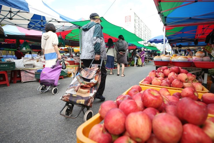 Visitors shop at a street market in Gwangju, South Jeolla Province, Sept. 25, where merchants have prepared fruits and other foods for the upcoming major Chuseok holiday next week amid the recent upsurge in COVID-19 infections. Yonhap