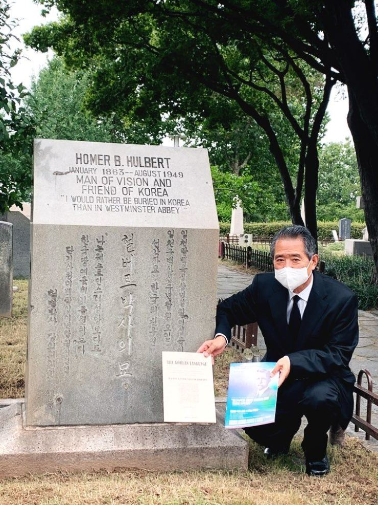 Kim Dong-jin, chairman of the Hulbert Memorial Society, poses with a book including the original copy of the influential educator's 1889 New-York Tribune article on the Korean alphabet, next to Hulbert's tomb in Seoul, Monday. Courtesy of Hulbert Memorial Society
