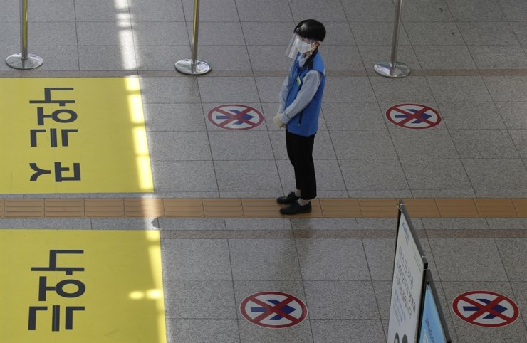 An employee wearing a face mask and face shield stands to guide passengers to maintain a one-way walk flow as a precaution against the coronavirus at the Seoul Railway Station in Seoul, Thursday, Sept. 10, 2020. AP