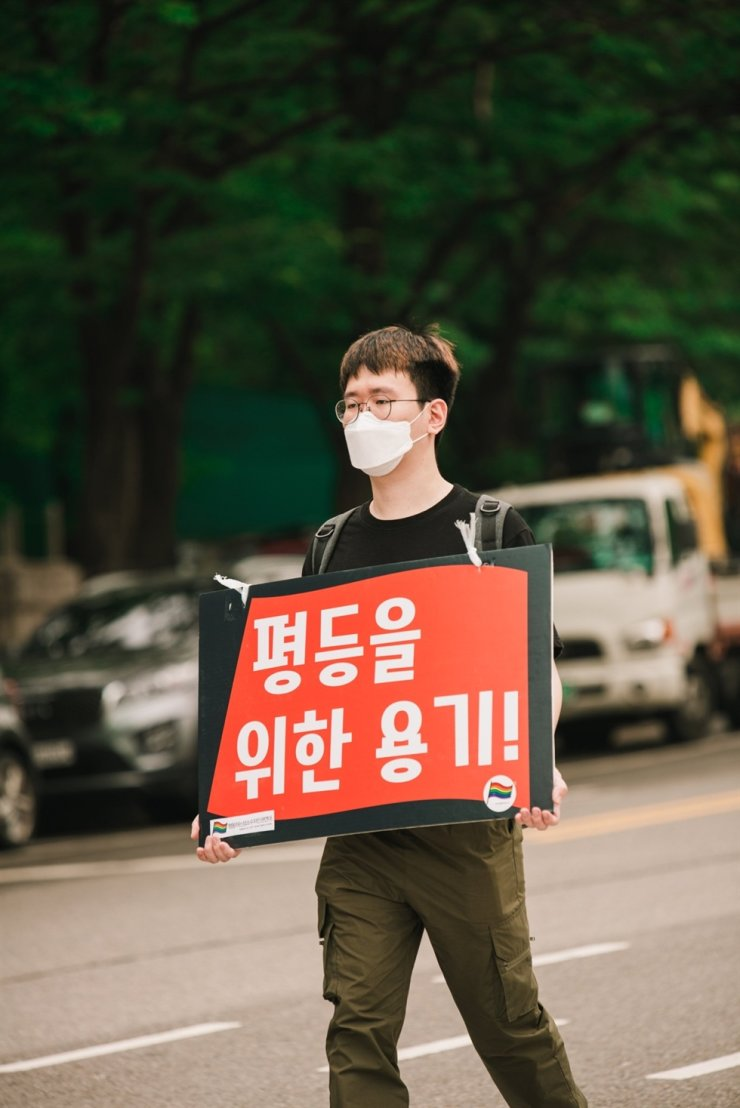 A gay man who asked to be named only with his initial J.W. marches at a pro-LGBT rally in Seoul in July. The sign he is holding reads 'Courage for Equality.' / Courtesy of Kang Josae