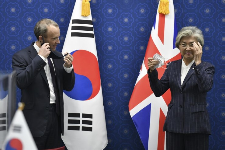 South Korea's Foreign Minister Kang Kyung-wha, right, and British Foreign Secretary Dominic Raab take off their face masks for a photo session during their meeting at the foreign ministry in Seoul Tuesday, Sept. 29, 2020. AP