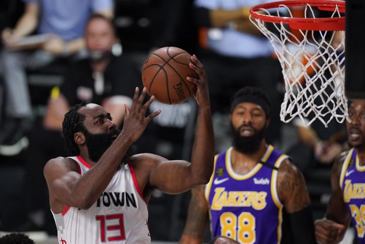 Houston Rockets' James Harden, front, drives to the basket ahead of Los Angeles Lakers' Markieff Morris, rear, during the first half of an NBA conference semifinal playoff basketball game in Lake Buena Vista, Fla., Friday. / AP-Yonhap