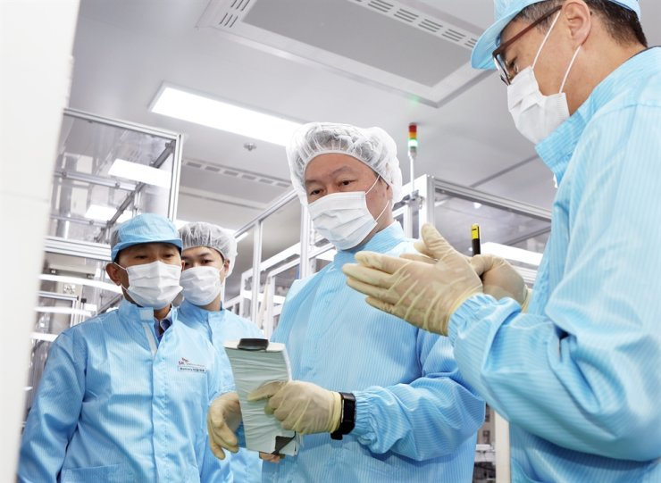 SK Group Chairman Chey Tae-won, center, looks at a battery cell at SK Innovation's plant in Seosan, South Chungcheong Province, April 19, 2019. Courtesy of SK Innovation