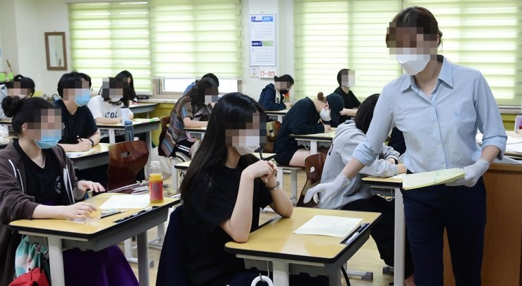 A teacher collects students' answer sheets during a mock university scholastic ability exam held at Yeouido Women's High School in Seoul, Wednesday. Yonhap