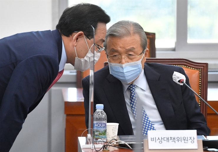 Main opposition People Power Party's emergency committee chief Kim Chong-in, right, listens to floor leader Rep. Joo Ho-young at the National Assembly in Seoul, Tuesday, during an online general meeting with party members from across the country. Yonhap