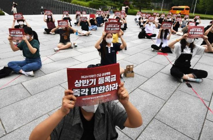 Students of Ewha Womans University hold signs calling for tuition fee refunds at the campus in central Seoul on June 29. / Korea Times photo by Hong In-ki
