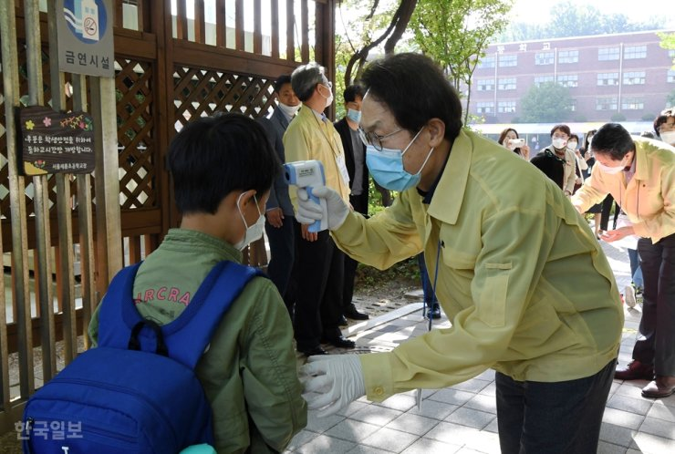 Cho Hee-yeon, right, the superintendent of the Seoul Metropolitan Office of Education, checks a student's temperature at Seryun Elementary School in Seoul in this Feb. 3 file photo. Korea Times photo by Hong In-ki