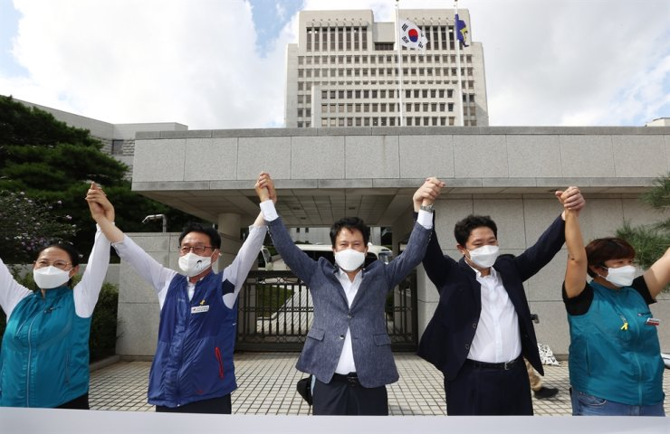 Members of the Korean Teachers and Education Workers Union (KTU) hold hands during a press conference in front of the Supreme Court in Seoul, Thursday. The Supreme Court annulled a decision by the former Park Geun-hye government to outlaw the progressive teachers' union for refusing to disallow membership to a handful of fired teachers. Yonhap