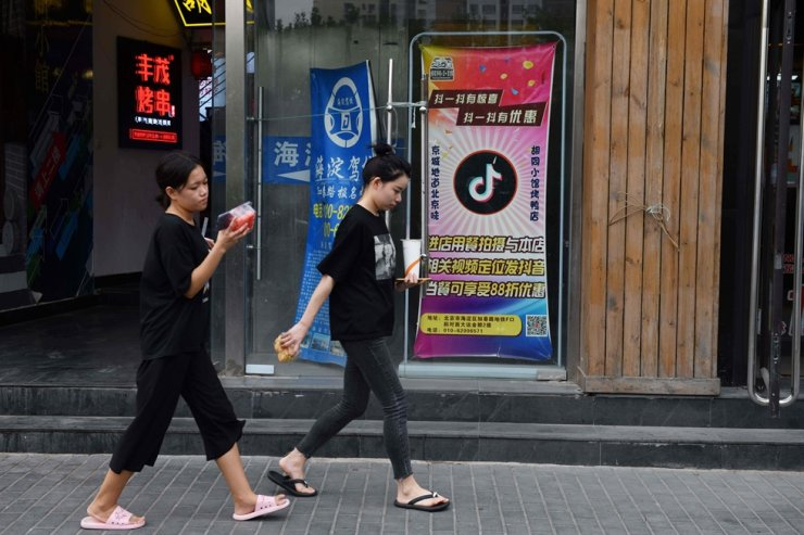 People walk past a restaurant with a TikTok logo displayed in the window in Beijing, Sept. 14, 2020. AFP
