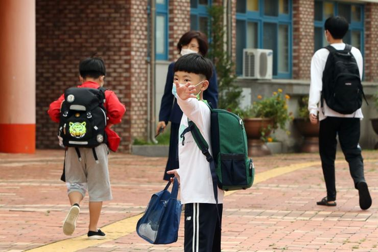 A student waves bye to his parents before class in an elementary school in Gwangju, Sept. 14. The school reopened previously providing online classes amid fears over the continuing spread of COVID-19. Yonhap