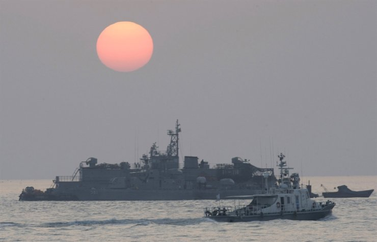 In this Dec. 22, 2010, file photo, a government ship sails past the South Korean Navy's floating base as the sun rises near Yeonpyeong island, South Korea. AP